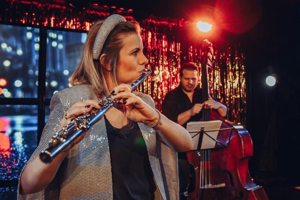 Kobieta gra na flecie. W tle mężczyzna gra na kontrabasie