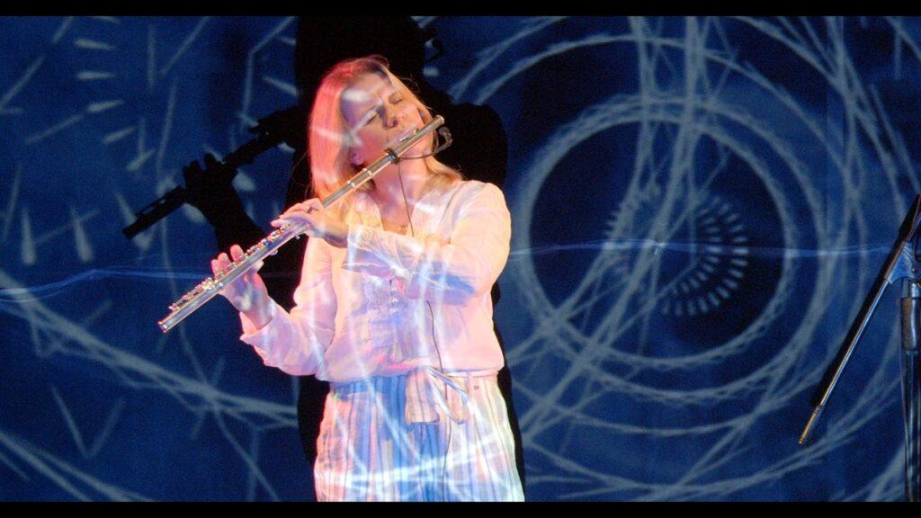 Artystka gra na flecie. W tle widać niebieskie wizualizacje.
