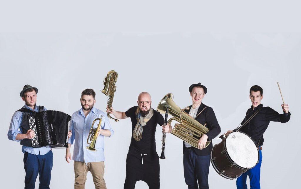 Pięcioro muzyków na białym tle trzyma w rękach instrumenty. Od lewej: akordeon, trąbka, saksofon i flet, tuba, werbel.