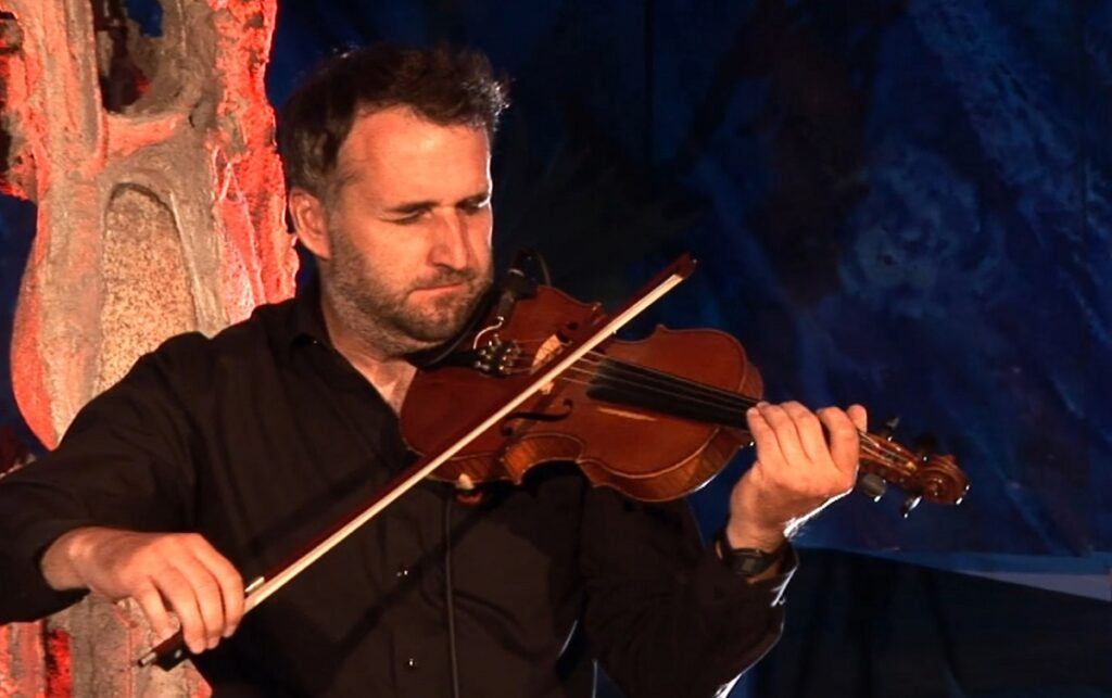 Mężczyzna w czarnej koszuli gra na skrzypcach