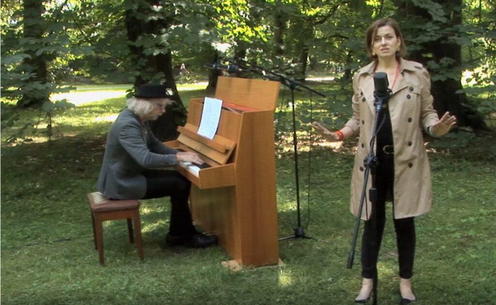 Zdjęcie wykonane w parku. Po prawej śpiewa wokalistka, Po lewej akompaniuje jej pianista.