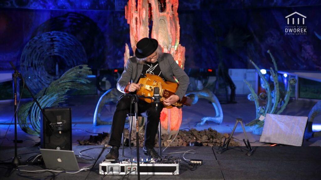 Mężczyzna gra na lirze korbowej w galerii rzeźby.