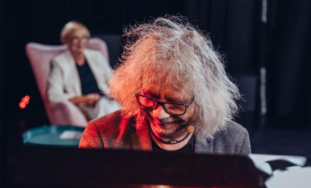 Na zdjęciu mężczyzna z siwą rozczorchaną fryzurą w okularach. Uśmiecha się grając na fortepianie. Za nim w tle kobieta w białym kostiumie siedzi na różowym fotelu.