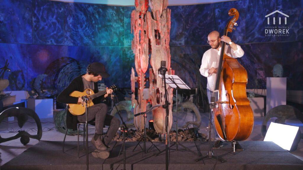 Na scenie dwóch muzyków. Po lewej siedzący na krześle męczyzna gra na gitarze, po prawej meżczyzna gra na kontrabasie.