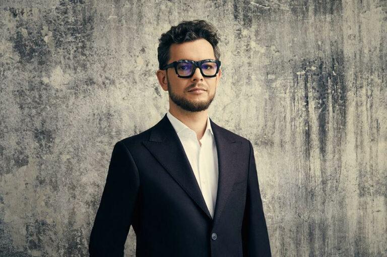 Mężczyzna w garniturze i okularach na szarym tle