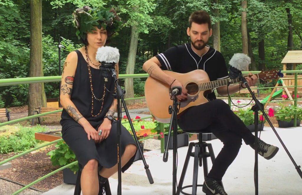 Na zdjęciu kobieta i mężczyzna. Kobieta po lewej śpiewa, mężczyzna po prawej akompaniuje na gitarze.