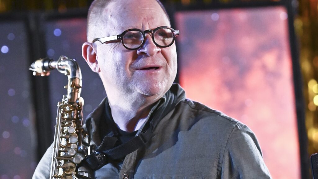 Mężczyzna w okularach spogląda w prawą stronę. W ręgach trzyma saksofon.