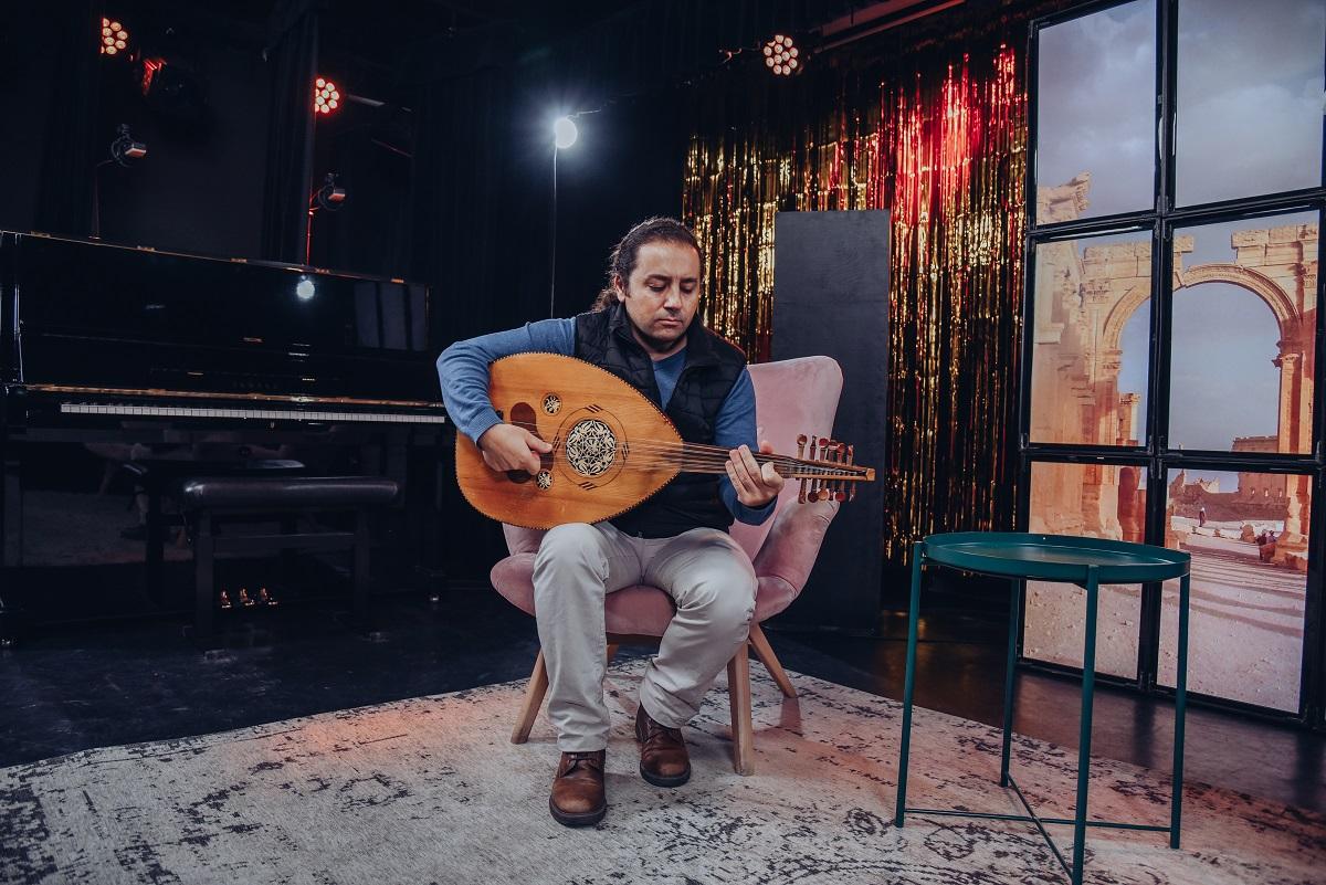 Na zdjęciu muzyk siedzi na fotelu i gra na lutni arabskiej zwanej Ud. Po prawej mały okrągły stolik. Za nim plan telewizyjny