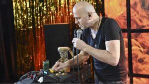 Mężczyzna śpiewa do mikrofonu i jednocześnie obsługuje urządzenie.