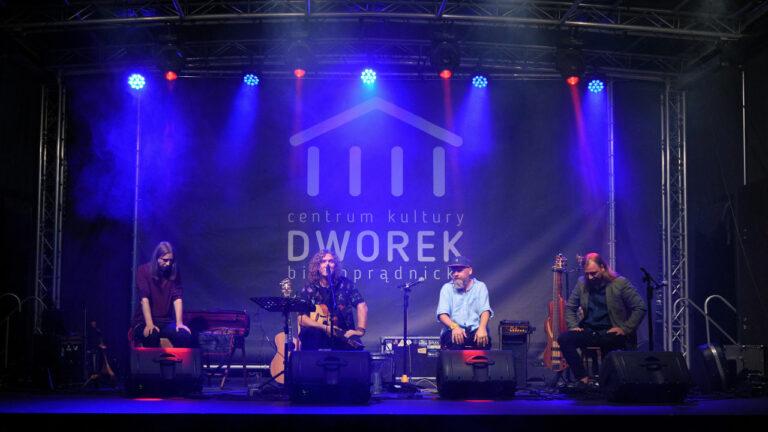 Na scenie czworo muzyków gra koncert. Oświetleni niebieskim światłem. W tle logotyp instytucji.