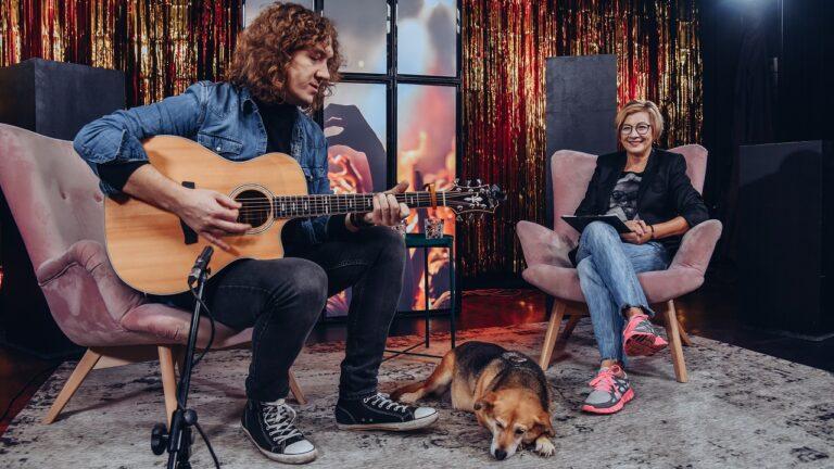 Od lewej mężczyzna gra na gitarze, na podłodze leży pies. Po prawej na fotelu siedzi kobieta.