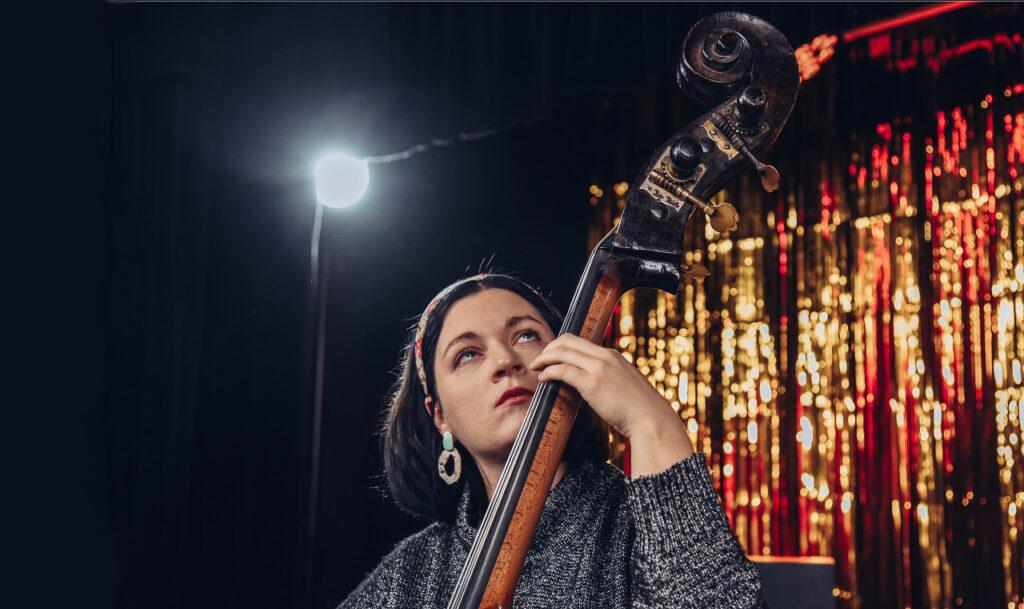 Kobieta gra na kontrabasie. W tle reflektor i słota scenografia.