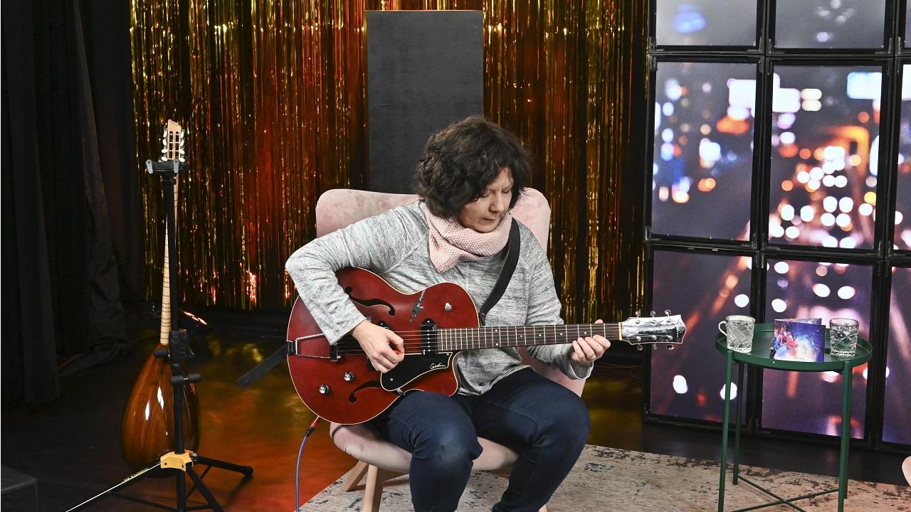 Kobieta siedząc na fotelu gra na gitarze