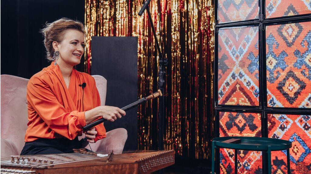 Uśmiechnięta kobieta siedzi na fotelu, w ręku trzyma instrument duduk.
