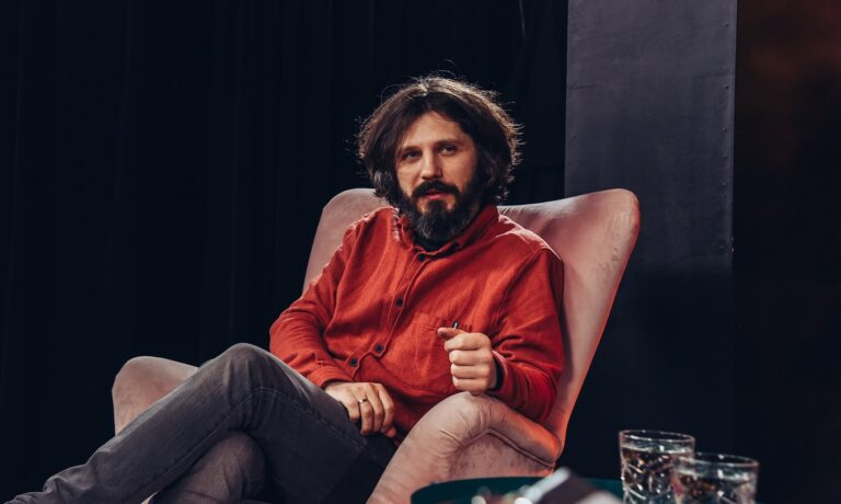 Mężczyzna siedzi na różowym fotelu