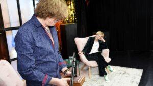 Na pierwszym planie mężczyzna gra na kalimbie. Na drugim kobieta siedzi na fotelu, przygląda się muzykowi.