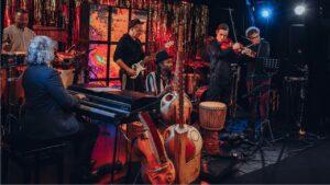 Na scenie siedmioro muzyków grających na różnych instrumentach