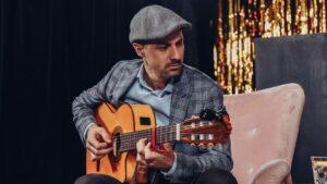 Mężczyzna siedzący na fotelu gra na gitarze.