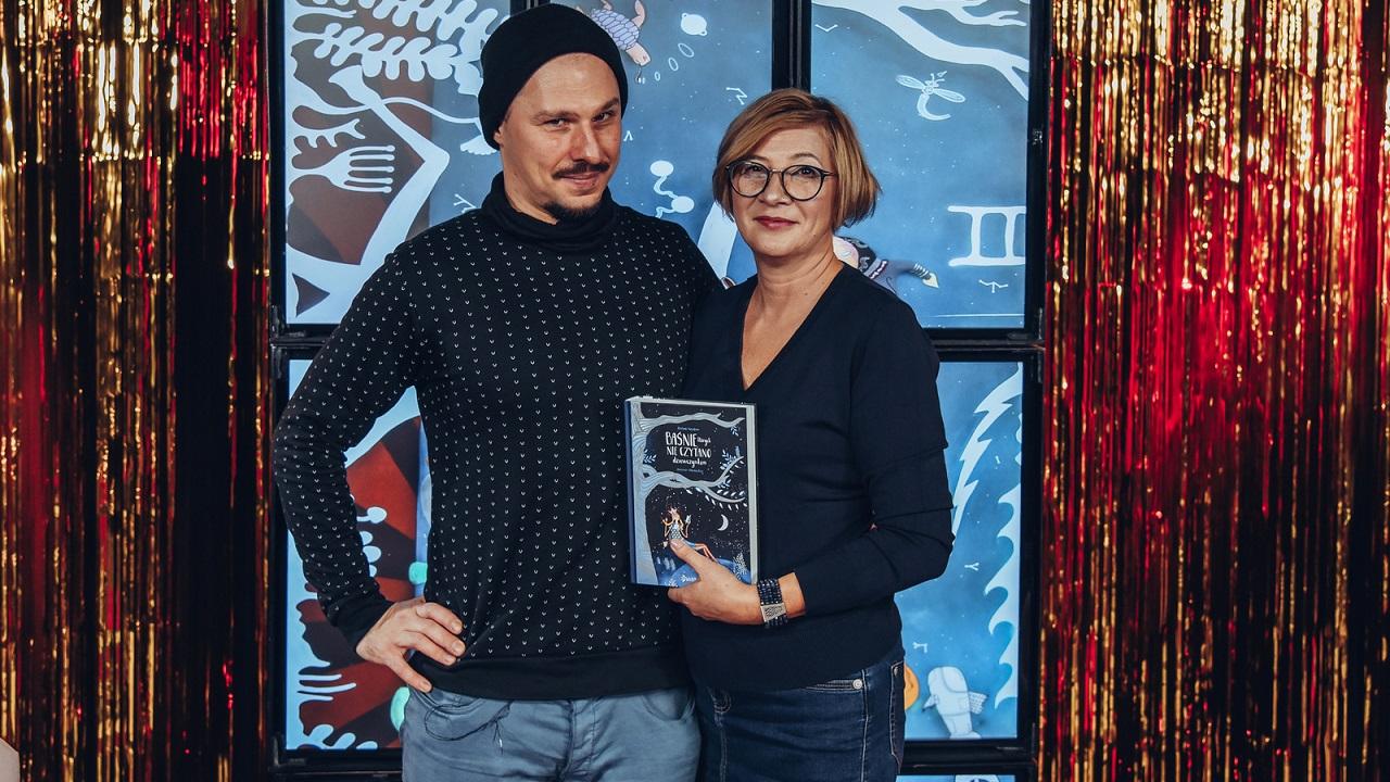 Meżczyna i kobieta stoją obok siebie. Patrzą w obiektyw, Kobieta trzyma w rękach książkę.