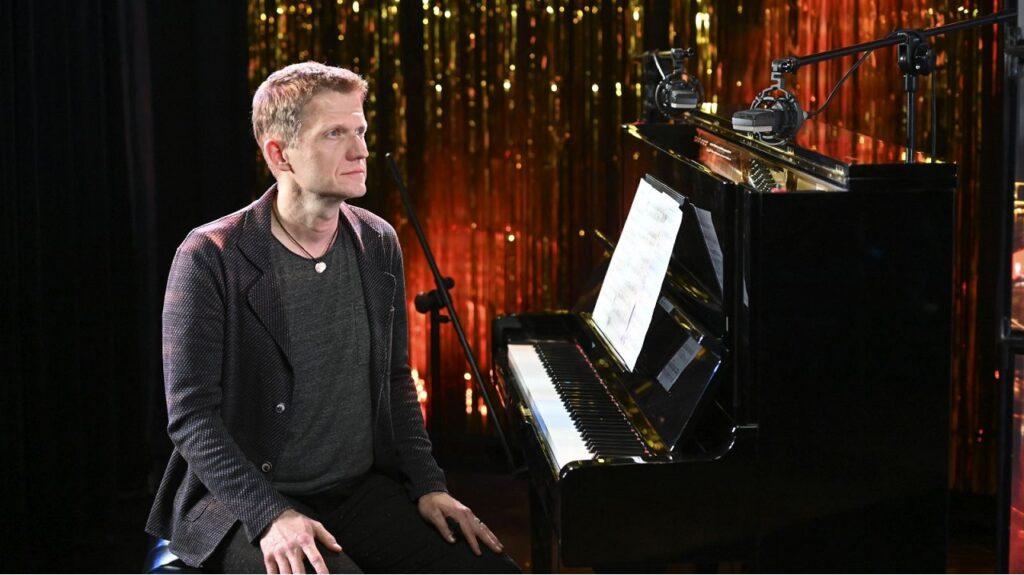 Mężczyzna siedzi przy fortepianie