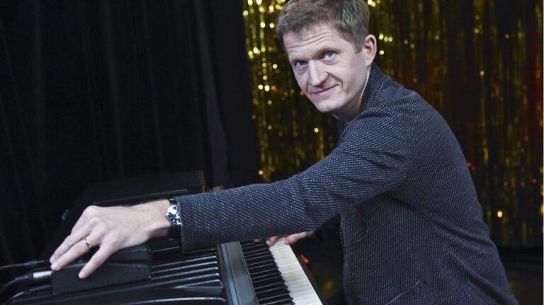 Mężczyzna gra na pianinie. Patrzy w stronę kamery.