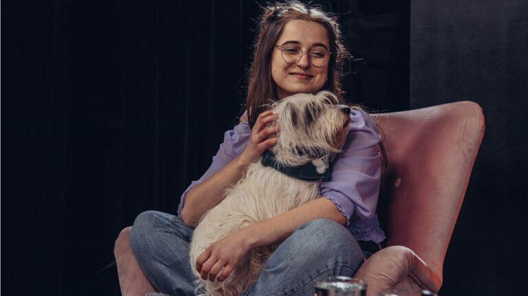 Kobieta siedzi na fotelu z psem na kolanach