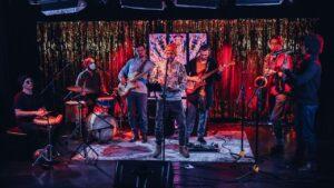 Zespół siedmiorga muzyków gra koncert na scenie
