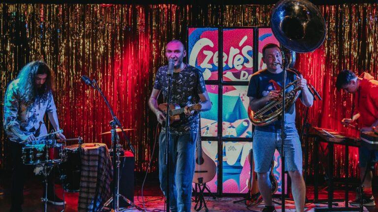 Na scenie zespół czterech muzyków gra koncert
