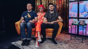 Na kanapie z powaznymi minami siedzi dwóch mężczyzn i w środku kobieta.