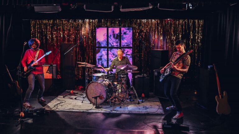 Trzech mężczyzn gra koncert na scenie