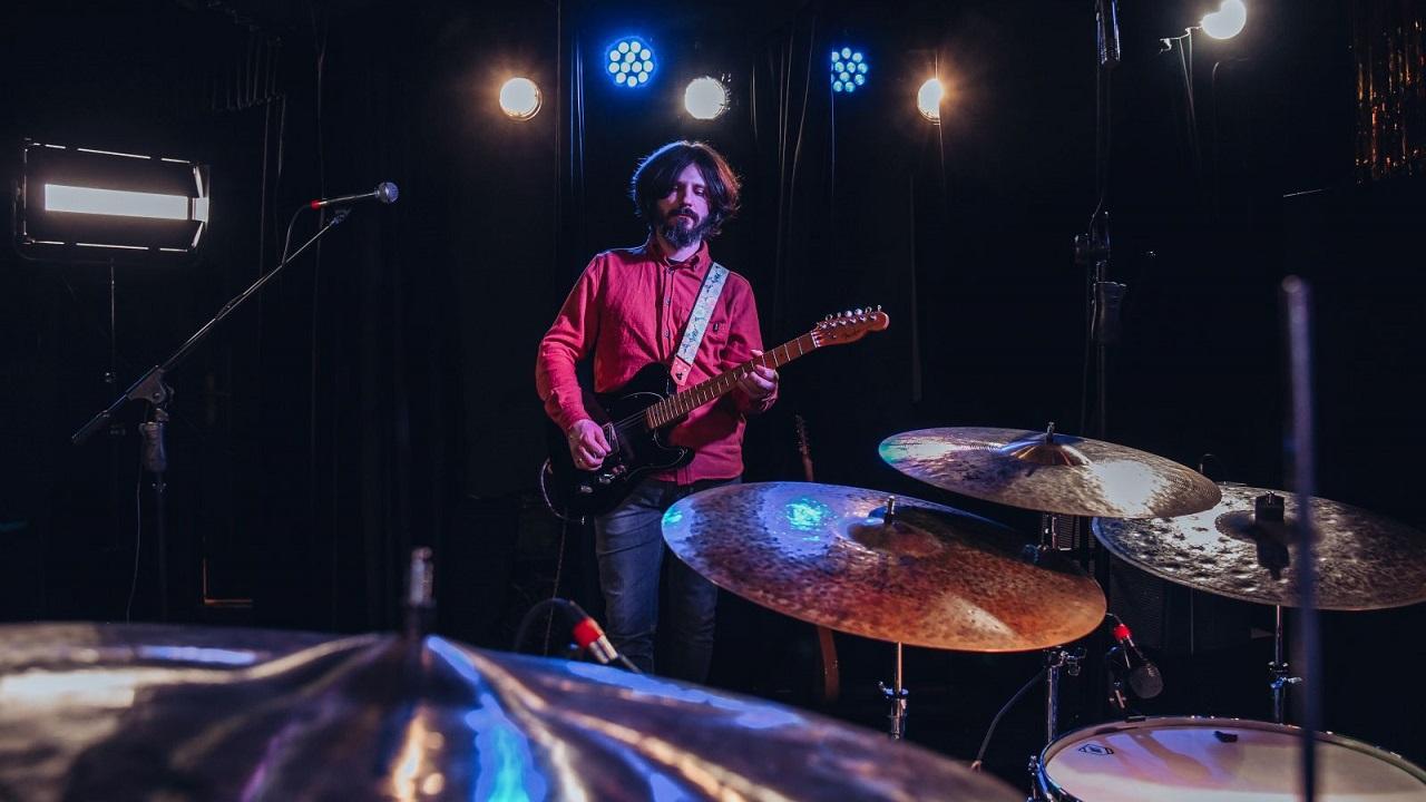 Na pierwszym planie talerze perkusyjne, za nimi stoi gitarzysta