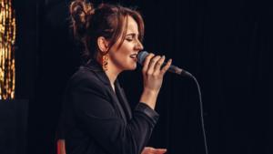 Kobieta odwrócona bokiem śpiewa do mikrofonu.