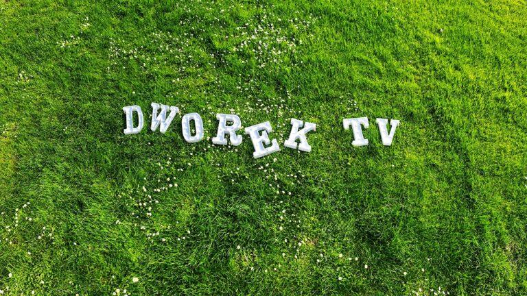 Biały napis dworek tv na trawie