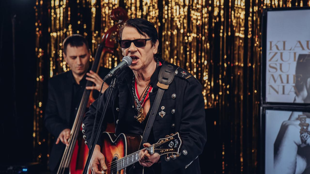 Mężczyzna w ciemnych okularach gra na gitarze i śpiewa
