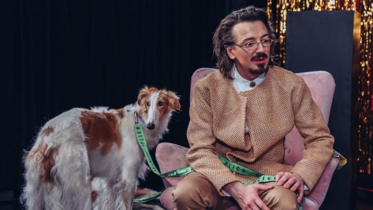 Po prawej mężczyzna w beżowym garniturze siedzi na fotelu. Po prawej stoi pies - chart.