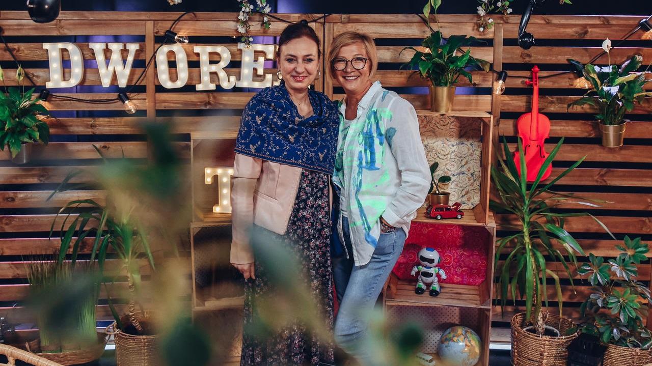 Dwie uśmiechnięte kobiety pozują do zdjęcia. W tle napis DWOREK TV