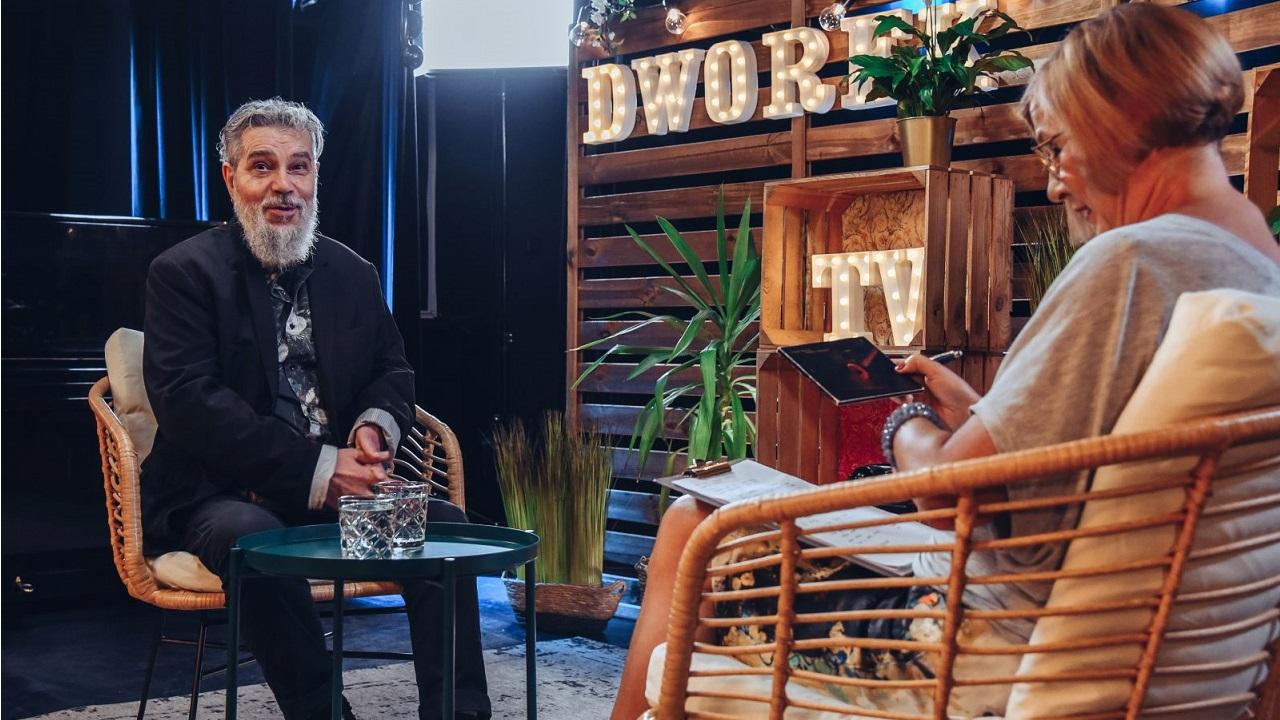 Po lewej stronie siedzi uśmiechnięty mężczyzna z brodą. Po prawej odwrócona tyłem kobieta siedząca na krześle.