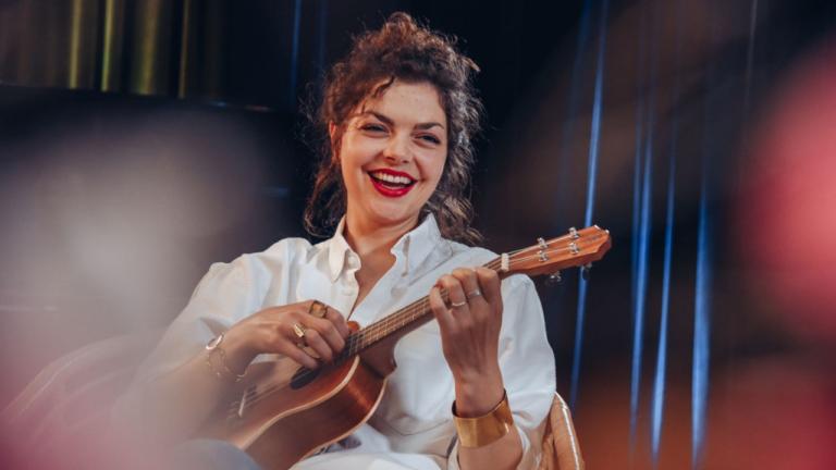 Uśmiechnięta kobieta gra na ukulele
