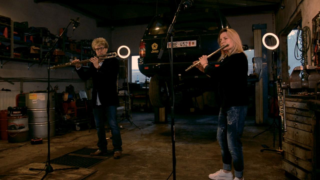 Kobieta i mężczyzna grają na fletach w warsztacie samochodowym
