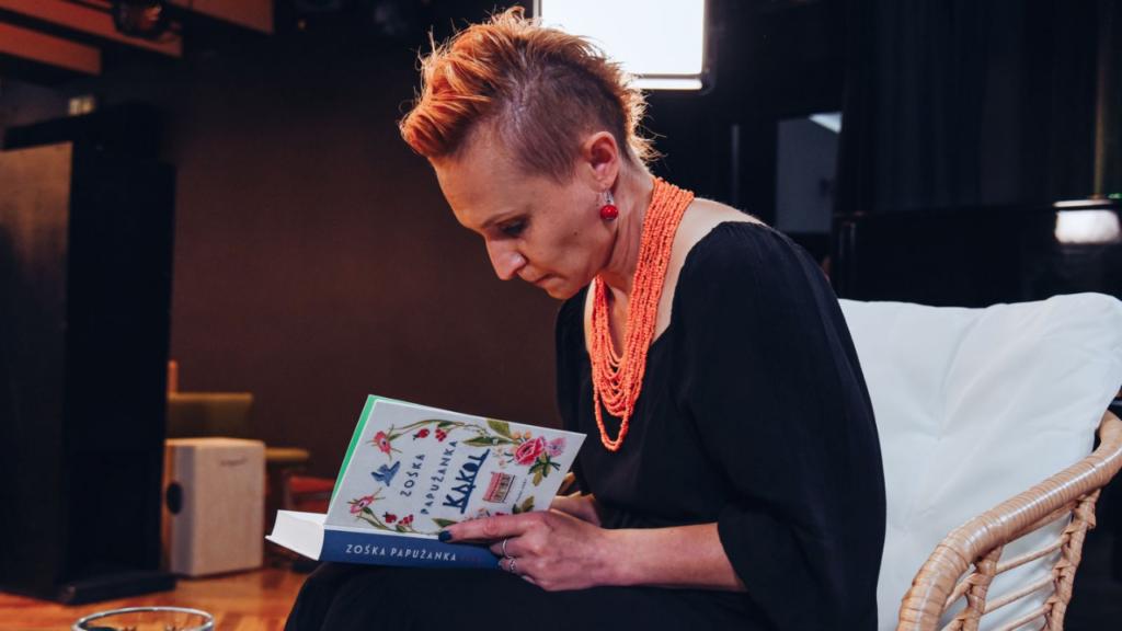 Kobieta pochylona nad książką podpisuje książkę